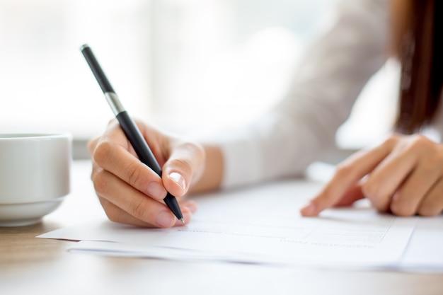Hand der geschäftsfrau schriftlich auf papier im büro Kostenlose Fotos