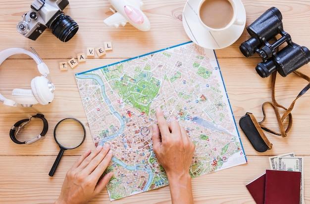 Hand der person, die auf standort auf karte mit tasse tee- und reisendenzubehör auf holzoberfläche zeigt Kostenlose Fotos