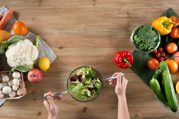 Hand der person, die frischen gesunden salat nahe vielzahl des gemüses und der früchte auf hölzerner küchenarbeitsplatte zubereitet Kostenlose Fotos