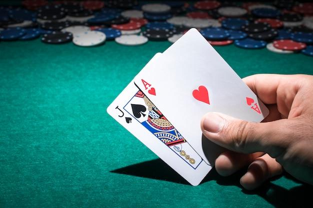 Hand der person, die pokerkarte im kasino hält Kostenlose Fotos