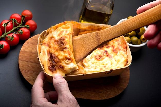 Hand der person, die scheibe der lasagne mit hölzerner spachtel nimmt Kostenlose Fotos