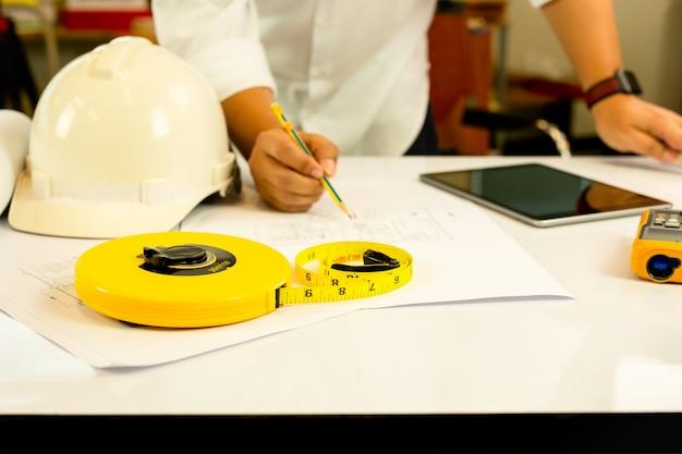 Hand des architekten arbeitend an plan mit tablet-computer auf tabelle. Premium Fotos