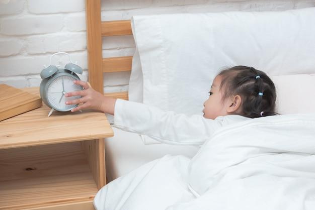 Hand des asiatischen mädchens morgens erreichend, um wecker auf dem bett abzuschalten Premium Fotos