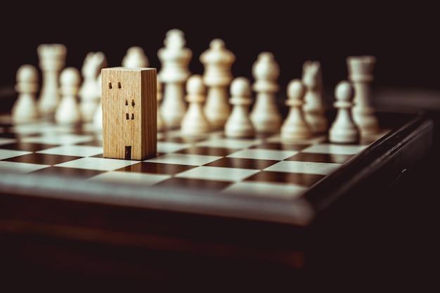 Hand des beweglichen schachs des geschäftsmannes zu den gebäude- und hausmodellen im schachspiel Premium Fotos