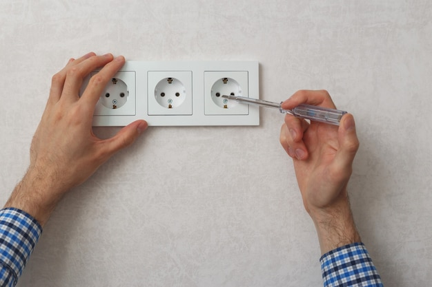 Hand des elektrikers mit phasentester-schraubendreher zur reparatur der steckdose. Premium Fotos