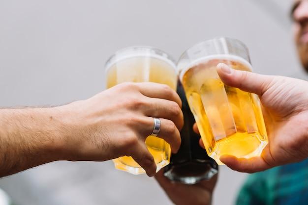 Hand des freundes, die glas bier röstet Kostenlose Fotos