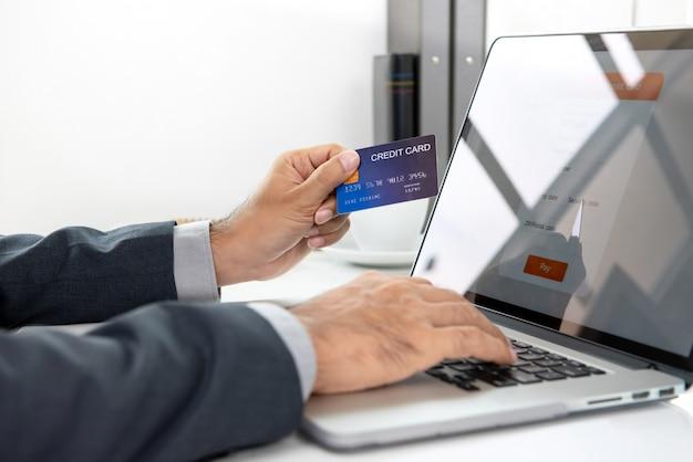 Hand des geschäftsmannes die kreditkarte halten, die online zahlung mit laptop-computer leistet Premium Fotos