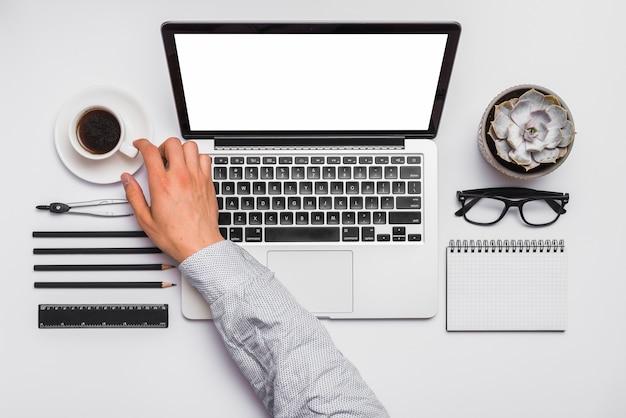 Hand des geschäftsmannes, die tasse kaffee auf schreibtisch nimmt Kostenlose Fotos
