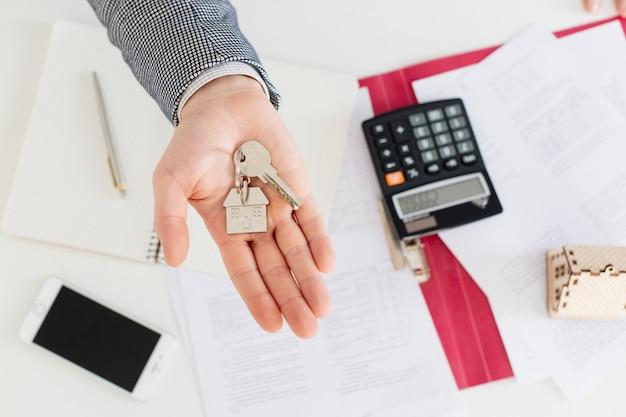 Hand des Grundstücksmaklers mit Schlüsseln Kostenlose Fotos