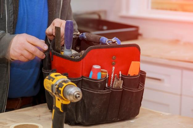 Hand des heimwerkers mit einer werkzeugtasche. Premium Fotos