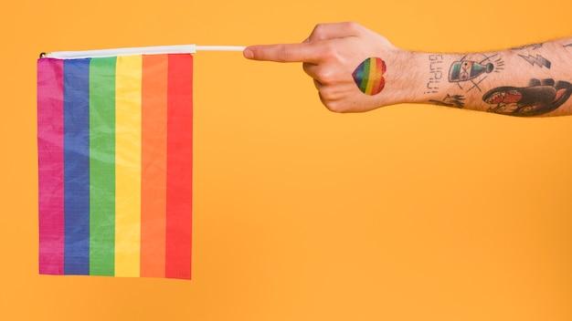 Hand des homosexuellen mannes, der lgbt-flagge hält Kostenlose Fotos