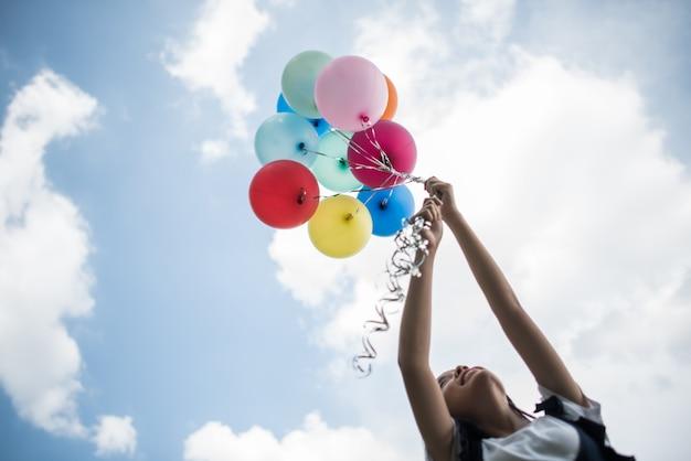 Hand des jungen mädchens, die bunte ballone hält Kostenlose Fotos