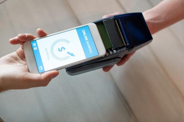 Hand des jungen mannes mit smartphone, der durch online-banking zahlt, während er sein mobiles gerät über dem vom kellner gehaltenen zahlungsautomaten hält Premium Fotos