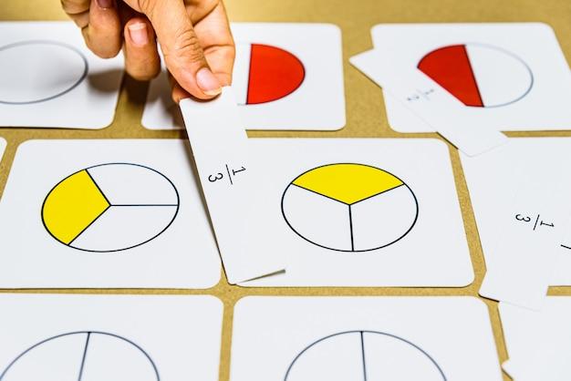 Hand des lehrers montessori-führer zeigt grafisch brüche mit mathematischen karten. Premium Fotos