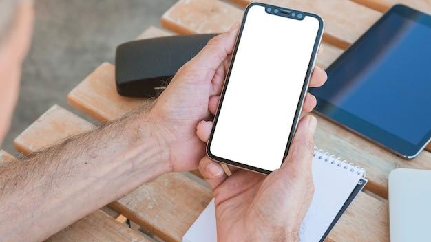 Hand des mannes, die smartphone mit leerem weißem schirm auf holztisch hält Kostenlose Fotos