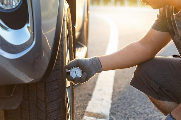 Hand des mannes luftdruck und füllende luft in den reifen seines autos überprüfend Premium Fotos