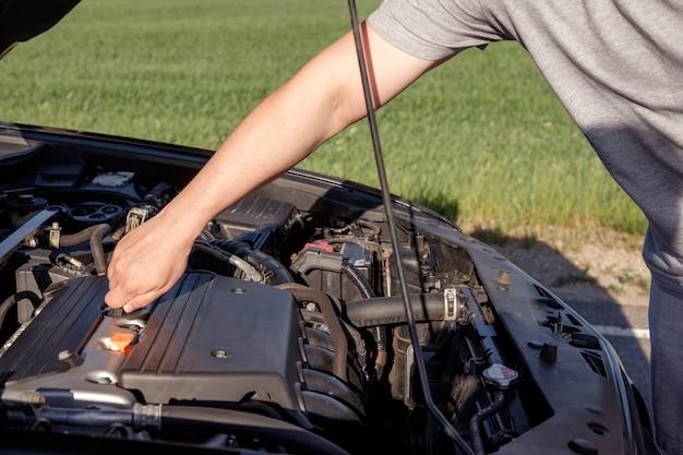 Hand des mannes, prepearing, um etwas öl im motor während der reise auf einer straße hinzuzufügen Premium Fotos