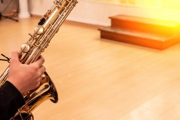 Hand des musikers jazzsaxophon während der live-aufführung auf der bühne spielend Premium Fotos