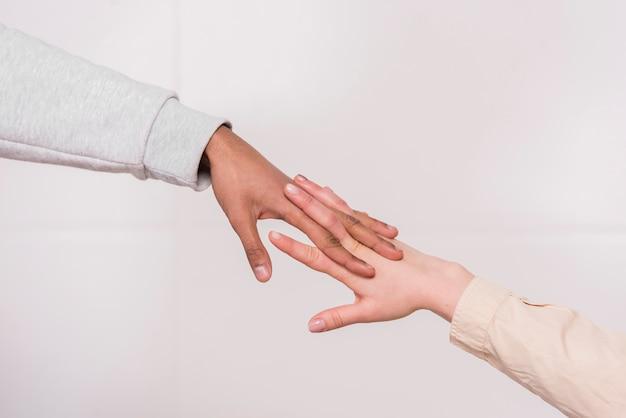 Hand des zwischen verschiedenen rassen paares gegen weißen hintergrund Kostenlose Fotos