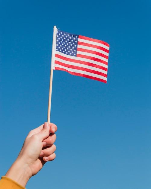 Hand, die amerikanische flagge auf blauem himmel hält Kostenlose Fotos