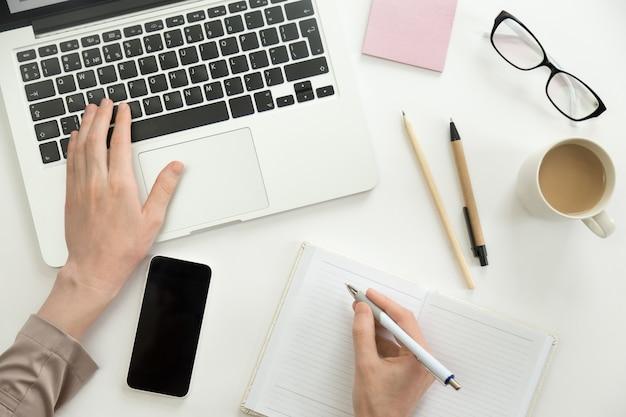 Hand, die an einem laptop arbeitet, ein anderer hält einen stift Kostenlose Fotos
