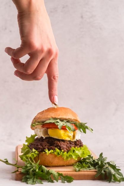 Hand, die auf einen köstlichen hamburger zeigt Kostenlose Fotos