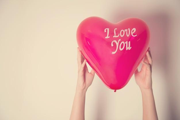Hand, die ballon und text ich liebe dich mit retro- filtereffekt hält Premium Fotos