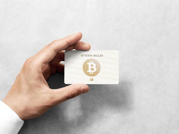 Hand, die bitcoin-karte mit geprägtem goldenem logo hält Premium Fotos