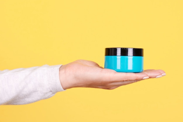 Hand, die blaues sahneglas lokalisiert hält Premium Fotos