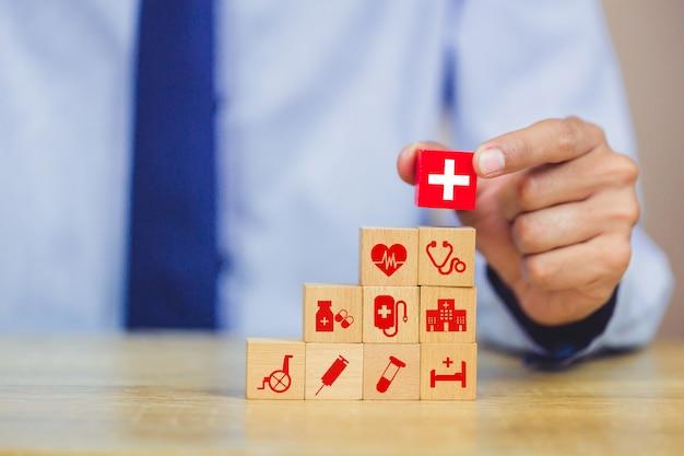 Hand, die den hölzernen block stapelt mit dem medizinischen ikonengesundheitswesen anordnet. Premium Fotos