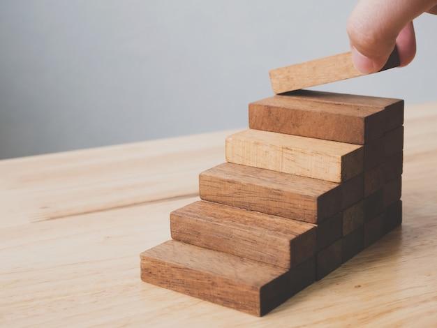 Hand, die den hölzernen blockstapeln als schritttreppe vereinbart Premium Fotos