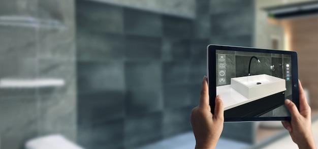 Hand, die digitales tablett im badezimmer hält Premium Fotos