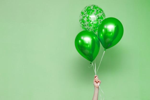 Hand, die drei helle bunte ballone innen hält. Premium Fotos