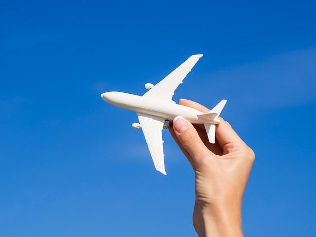Hand, die ein flugzeug im himmel hält Kostenlose Fotos