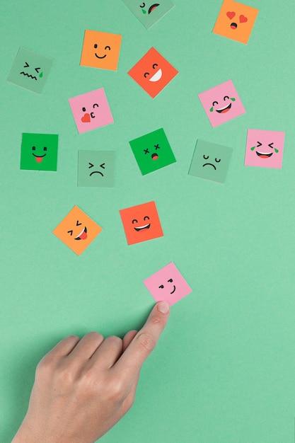 Hand, die ein quadratisches lächelndes gesicht berührt Kostenlose Fotos
