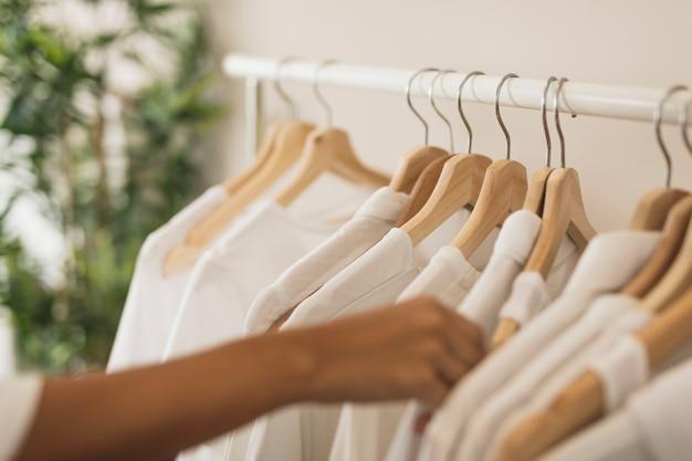 Hand, die ein weißes hemd von der garderobe wählt Kostenlose Fotos