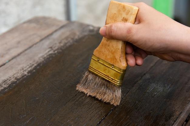Hand, die eine bürste hält malende hölzerne bauholzbretter tauchen mit hölzernem fleck auf Premium Fotos
