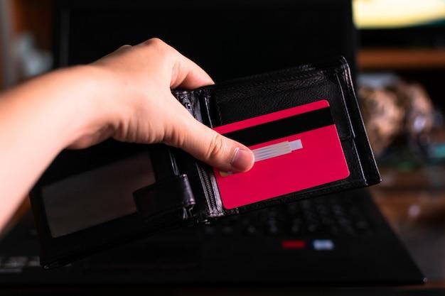 Hand, die eine geldbörse und eine kreditkarte mit einem laptop hält Premium Fotos