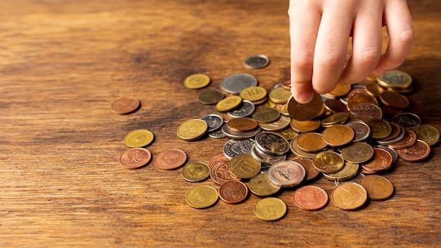 Hand, die eine münze von einem stapel hält Kostenlose Fotos