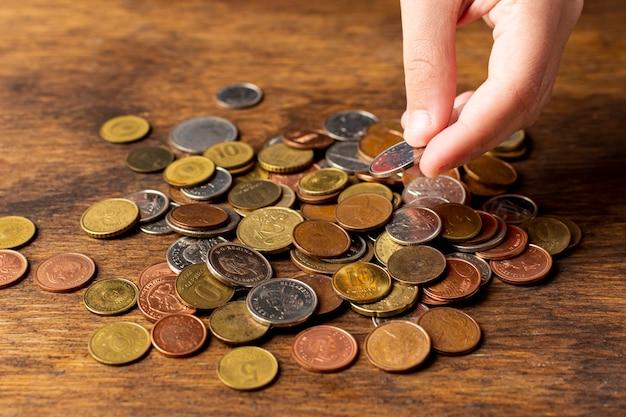 Hand, die eine münze von einer hohen ansicht des stapels hält Kostenlose Fotos