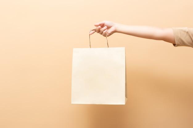 Hand, die eine papiertüte lokalisiert auf hintergrund hält Premium Fotos