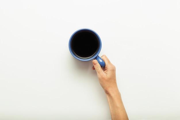 Hand, die eine tasse mit heißem kaffee auf einem blauen hintergrund hält. frühstückskonzept mit kaffee oder tee. guten morgen, nacht, schlaflosigkeit. flache lage, draufsicht Premium Fotos