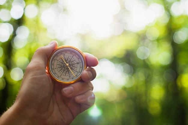 Hand, die einen kompass mit unscharfem hintergrund hält Kostenlose Fotos