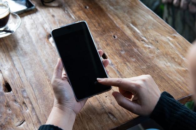 Hand, die einen smartphone auf hölzerner tabelle hält und verwendet. Premium Fotos