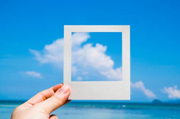 Hand, die einen sofortigen fotorahmen gegen blauen himmel anhält Kostenlose Fotos