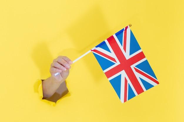 Hand, die englische flagge vom gelben zerrissenen papier hält. flagge des vereinigten königreichs in der hand. Premium Fotos