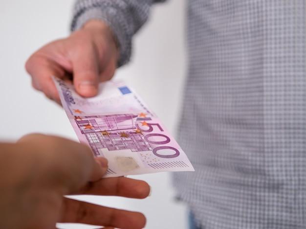 Hand, die geld- banknote des euros 500 gibt. Premium Fotos