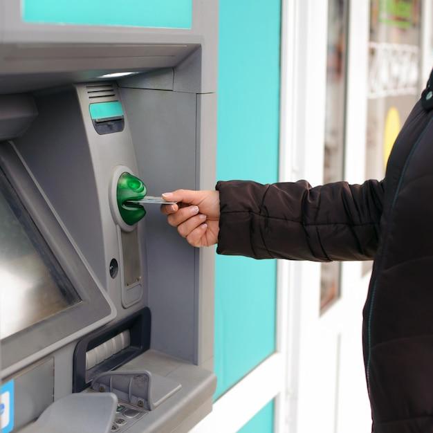 Hand, die geldautomatenkarte in bankautomaten einführt, um geld abzuheben Premium Fotos