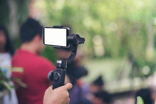 Hand, die gimbal mit smartphoneaufzeichnungsvideo hält Kostenlose Fotos