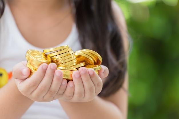 Hand, die goldenes münzenkonzept auf grünem hintergrund hält Premium Fotos